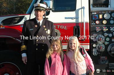 Bristol 2nd Assistant Fire Chief Tim Miller escorts Elizabeth Benner and Gabby Vincentsen out of the fire truck. The fire trucks picked up the students at home and arrived at school with lights and sirens Oct. 9. (J.W. Oliver photo)
