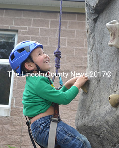 Caleb Busby, 5, of Damariscotta, grins with excitement as he tries out the Camp Kieve climbing wall at Applefest Oct. 5. (D. Lobkowicz photo)