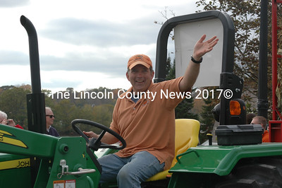 Damariscotta Pumpkinfest co-founder Buzz Pinkham greets paradegoers from his giant-pumpkin-towing tractor. (J.W. Oliver photo)