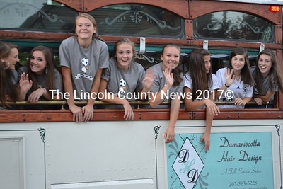 From left to right, Chloe Hallowell, Alyssa Smith, Barrett Campbell, Hayden Campbell, Alyx York, Cate Organ, Courteney Peabody, and Michaela Peabody whoop it up on the trolley ride from downtown Damariscotta to the Newcastle private school during Lincoln Academy's Homecoming Parade. (Sherwood Olin photo)