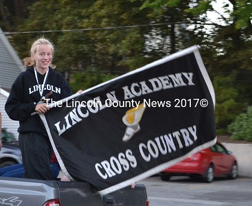 Essie Martin waves the flag for Lincoln Academy's cross country team. (Sherwood Olin photo)