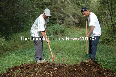 Josh McInnis (left) and Matthew Tedford of the Lincoln-Sagadahoc Public Works Crew spread mulch on a trail at the Central Lincoln County YMCA. The public works crew, which consists of inmates from Two Bridges Regional Jail, provides free labor for local nonprofits and affords prisoners an opportunity to earn time off their sentence while serving the community. (J.W. Oliver photo)