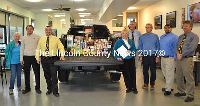 "Wiscasset Ford employees begin a ""Stuff the Truck"" food collection campaign to help St. Philip's Church provide Thanksgiving meals for area families. From left are: Lois Atwood, Nicholas Lamoreau, Spencer Grinnell, Gretchen Burgleigh-Johnson, Scott Lane, John Green, Toran Castro and Jeff Allen. (Kathy Onorato photo)"