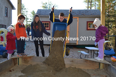 Friends Forever delegate Josh Minta fills the sandbox at Coastal Kids Preschool Oct. 29 as Bronagh Murray and Coastal Kids students look on. The Friends Forever program brings Protestant and Roman Catholic teenagers from Northern Ireland to Maine to promote peace in the region. The two-week stay includes service projects, like this one, in the host community. (J.W. Oliver photo)