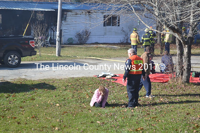 Waldoboro Police Chief Bill Labombarde stands by as Elizabeth Cunningham weeps in front of a mobile home destroyed on Nov. 14 in a fire investigators say was intentionally set. Cunningham lived in the mobile home with her son and their roomate Eric Buckley (behind Labombarde). (D. Lobkowicz photo)