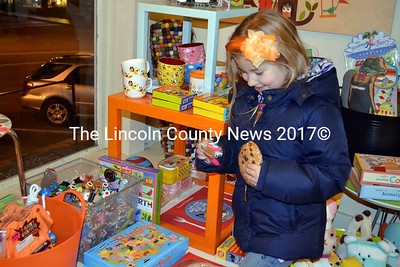 With a cookie in one hand, Eliana McLeod visits the children's corner at Rock Paper Scissors on Main Street in Wiscasset Nov. 30.  (Kathy Onorato photo)