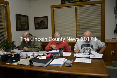 Westport Island selectmen work in the evening, reviewing the town's 9-1-1 listing are (from left), Selectmen Ross Norton, George Richardson, and Gerald Bodmer. (Charlotte Boynton photo)