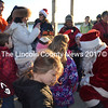 Santa arrives at the pier in Wiscasset Dec. 7, greeted by anxious youngsters. (Kathy Onorato photo)