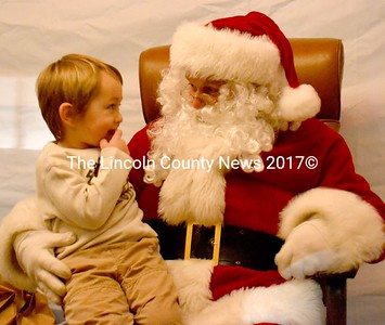 Bryson Luce, 3, sits on Santa Claus' lap Dec. 22. After a little discussion, Luce agreed a toy firetruck might make a better gift than one of the full sized ones parked nearby.  (D. Lobkowicz photo)