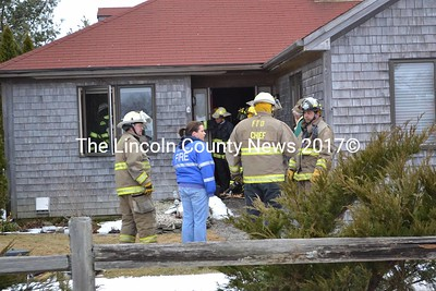 Waldoboro firefighters are observed through the picture window, and at the front door entry way, breaking down a wall searching for a fire. (K. Fletcher photo)