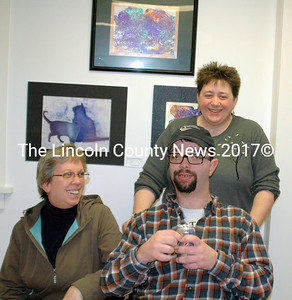 "Martha Holzwarth, Andy Richards and Gina Hoffses discuss Andy's ""Cats"" (behind) at the Mobius Creative Expressions Art Show."