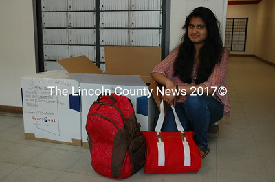 Lincoln Academy exchange student Sammia Nasrin prepares to mail two large boxes to Pakistan containing 12 backpacks full of school supplies. (J.W. Oliver photo)