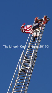 Atop the Waldoboro Fire Department's 100-foot ladder, selectman and volunteer firefighter James Bodman unfurls the U.S. flag. (Shlomit Auciello photo)