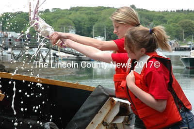 Julianna Preston (left) and Jillian Page christen Nichols and Dimes before the South Bristol School boat launch June 14. (J.W. Oliver photo)