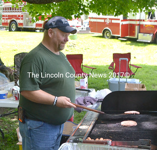 Dresden Fire Chief Steve Lilly flips burgers as part of the department's fundraising barbeque at Summerfest. (D. Lobkowicz photo)