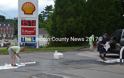 Newcastle Fire Chief Clayton Huntley (right) and vehicle owner Michael Horst (left) put down absorbent pads to sop up spilled gasoline on July 11. (D. Lobkowicz photo)