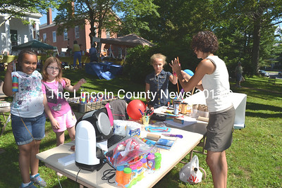 Children enjoy making pinatas at this year's Summerfest. Left to right are Nakira Rembert, Marguerita Fairfield, Aroura Rock. Stacey Vannah, far right, headed up the children's activities. (Kathy Onorato photo)
