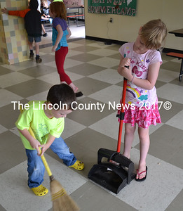 Its not all fun and games. Nick Maney and Emily Gilliam have sweeping duty after lunch at Wiscasset's summer camp on Monday, July 29. (Kathy Onorato photo)