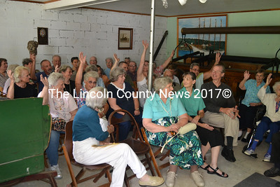 Descendents of Conrad Heyer raise their hands at the opening of the Heyer family exhibit at the Waldoborough Historical Society Museum on Aug. 18. (D. Lobkowicz photo)