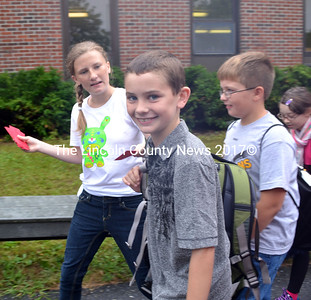 Wiscasset Middle School Civil Rights Team member Ari Mills, hands a bookmark to Aidan Foley on the first day of school.  (Kathy Onorato photo)
