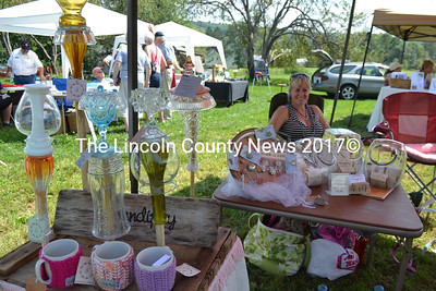 One of several vendors at the Medomak River Festival, Tiffany Hirst sits in the shade with many products from the Medomak River Community Market.  (D. Lobkowicz photo)
