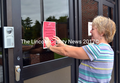 With a new security measure  installed, Wiscasset High School's secretary Shelley Schmal places instructions for entering the school.  (Kathy Onorato photo)