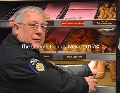 Waldoboro Police Chief Bill Labombarde captures runaway Gingy the Gingerbread Man as he attempts to free his cousins, the croissants, from Dunkin' Donuts in Waldoboro Dec. 13. (D. Lobkowicz photo)
