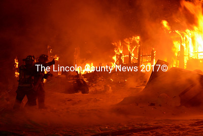 In the blowing snow, two Waldoboro firefighters prepare to put the first water on a burning mobile home on Gross Neck Jan. 2. (D. Lobkowicz photo)
