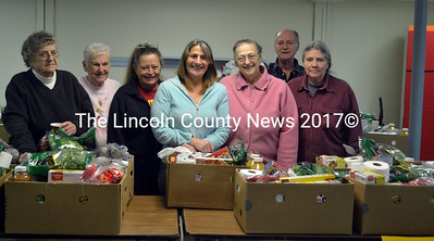 Whitefield Food Pantry volunteers, from left, Mary Grady, Emily Jones, Phyllis Wheeler, Becky Morton, Mary Lemieux, Earl Lemieux, and Anita Johns prepare food boxes for distribution at the food pantry's new location at  St. Denis Hall on Grand Army Road.  (Kathy Onorato photo)