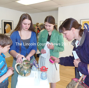 John Henry, Mary Catherine, Thalia and Allison Eddy-Blouin (left to right) admire the ceramic flowers made by Lincon Academy Senior Mary Catherine on display at River Arts.