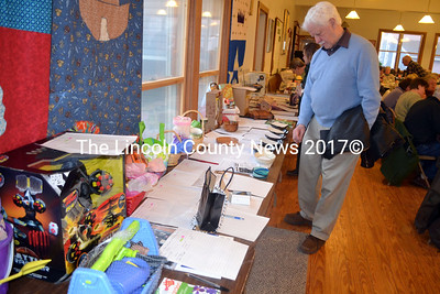 District 61 State Rep. Bruce McDonald looks over the many items up for auction as part of a Feed Our Scholars fundraiser at St. Philip's Church in Wiscasset April 5. (Kathy Onorato photo)