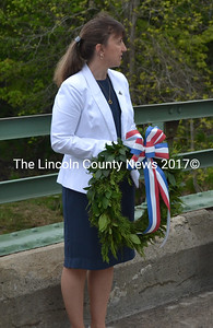 Waldoboro Town Clerk Linda Perry stands on the Main Street bridge with the memorial wreath she would later toss into the Medomak. (D. Lobkowicz photo)