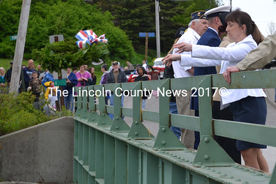 Waldoboro Town Clerk Linda Perry tosses a memorial wreath into the Medomak River as part of the town's Memorial Day celebration. See more coverage on page XX. (D. Lobkowicz photo)