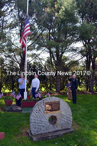 Glenn Angell (left) and Jerry Maldovan raise the flag at Whitefield's veterans memorial as retired U.S. Army Capt. Stephen Smith salutes. (Kathy Onorato photo)