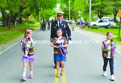 Nobleboro Brownies (from left) Isobel Petersen, Emily Boone, and Jasmine Brown carry flowers to place at  memorials along the route of the Twin Villages Memorial Day parade. James H. O'Brien, chaplain of the Newcastle Fire Department, provides an escort. (Tim Badgley photo)
