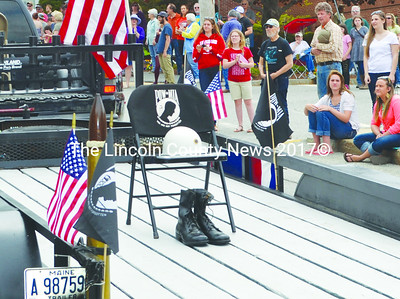 An empty chair, a helmet and a pair of combat boots serve as stark reminders of U.S. military missing in action and prisoners of war in the Twin Villages Memorial Day parade. (Tim Badgley photo)