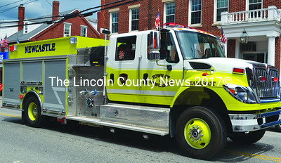 Newcastle firefighters wave from the cab of their truck in the Twin Villages Memorial Day parade. (Tim Badgley photo)