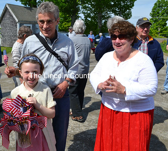 Zoe Soule hands out American flags to Whitefield Selectmen Tony Marple and Sue McKeen at Whitefield's Memorial Day service. (Kathy Onorato photo)