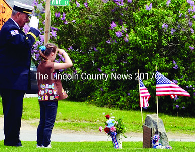 James H. O'Brien, chaplain of the Newcastle Fire Department; and Nobleboro Brownie Jasmine Brown place flowers at the veterans memorial in Damariscotta during the Twin Villages Memorial Day parade. (Tim Badgley photo)