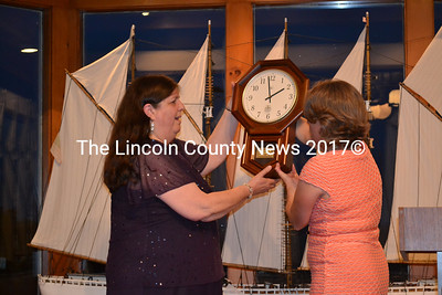 Retiring Wiscasset Middle School Principal Linda Bleile is presented with an engraved clock commemorating her 41 years of service. Making the presentation is  Wiscasset Middle School secretary Stacey Souza. (Kathy Onorato photo)