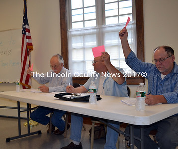 Dresden's Board of  Selectmen, from left, Philip Johnston, Gerald Lilly, ,and Allan Moeller raise their cards during town meeting June 14. (Kathy Onorato photo)