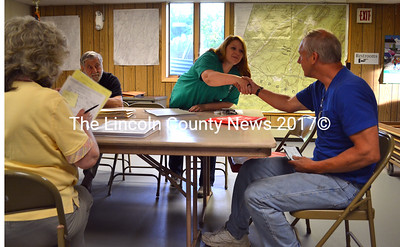 Edgecomb Selectman Jessica Chubbuck offers a hand shake to Maurice Hyson, who purchased 48 acres of land from the Town of Edgecomb for $1,014 June 16. (Kathy Onorato photo)