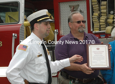 Somerville Assistant Fire Chief Tim Dostie presents Scott Emery with a plaque in recognition of the contribtion of Cecil Brann's heirs in purchasing a new fire truck for Somerville. (Eleanor Cade Busby photo)