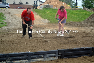 Lewis Shorey and Lisa Kalloch use rakes to level the ground at the Whitefield School July 3. (Kathy Onorato photo)