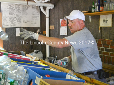 Rick Weymouth tosses a bottle at his business, Waldoboro Redemption Center. With the closure of Goodnow's Variety in Waldoboro and the building the two businesses occupied going up for sale, he is unsure of his business's future. (D. Lobkowicz photo)