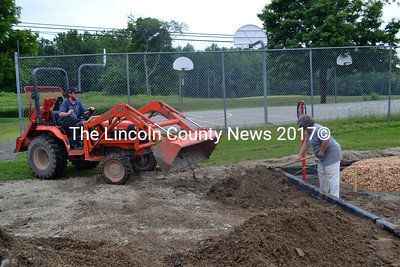 Moving the soil at the site of the  Whitefield Elementary School playground on July 3 are Joshua Shorey (left) and Sue Peaslee. (Kathy Onorato photo)