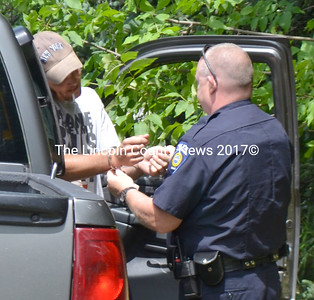 Waldoboro Police Officer Larry Hessletine arrests Keith Mein July 10. (D. Lobkowicz photo)