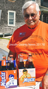 Merrill Lewis of Manchester, N.H., Ambassador of the New England Moxie Congress, a fan club of the soft drink, sells four-packs at Fernald's in Damariscotta as part of the eatery's annual Moxie celebration. (Tim Badgley photo)