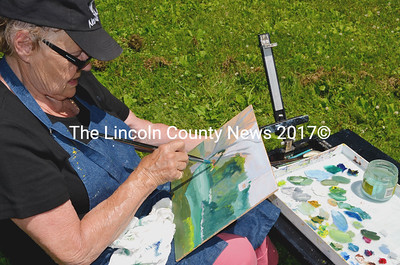 Plein Air Painters - The Real Thing group leader Carol Smith, of Damariscotta, worked on painting the landscape viewed from her perch on a Glidden Street lawn in Newcastle overlooking the Damariscotta River July 11. (Tim Badgley photo)