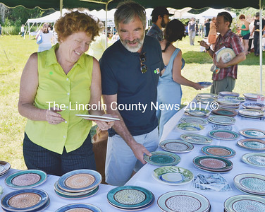 From left, Deb Arter of Damariscotta and Tomlin Coggeshall of Newcastle select their Salad Days plates at the annual fundraising event for Watershed Center for the Ceramic Arts in Newcastle July 12. (Tim Badgley photo)